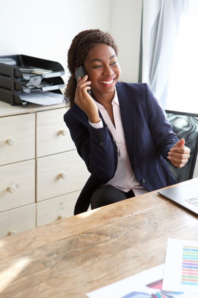 young black businesswoman talking on cellphone in office